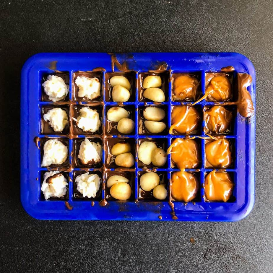 Mini ice cube tray filled with melted chocolate and fillings.