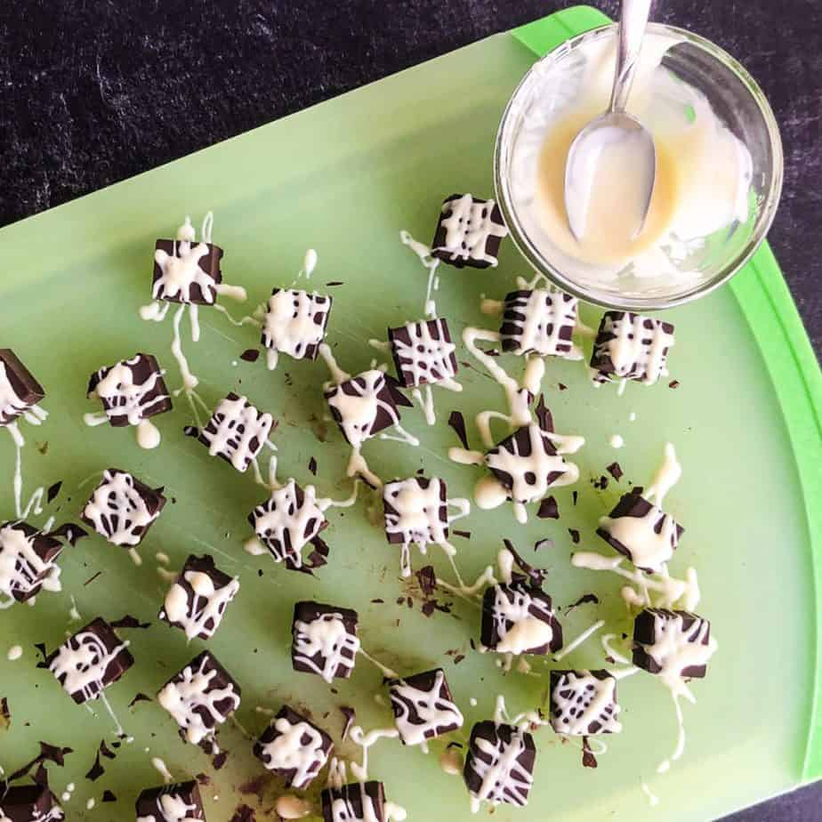Chocolates on a green cutting board drizzled with white chocolate.