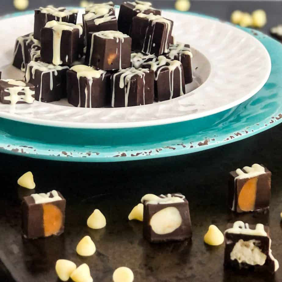 Filled chocolates on a white plate with chocolates cut in half in foreground to reveal fillings.
