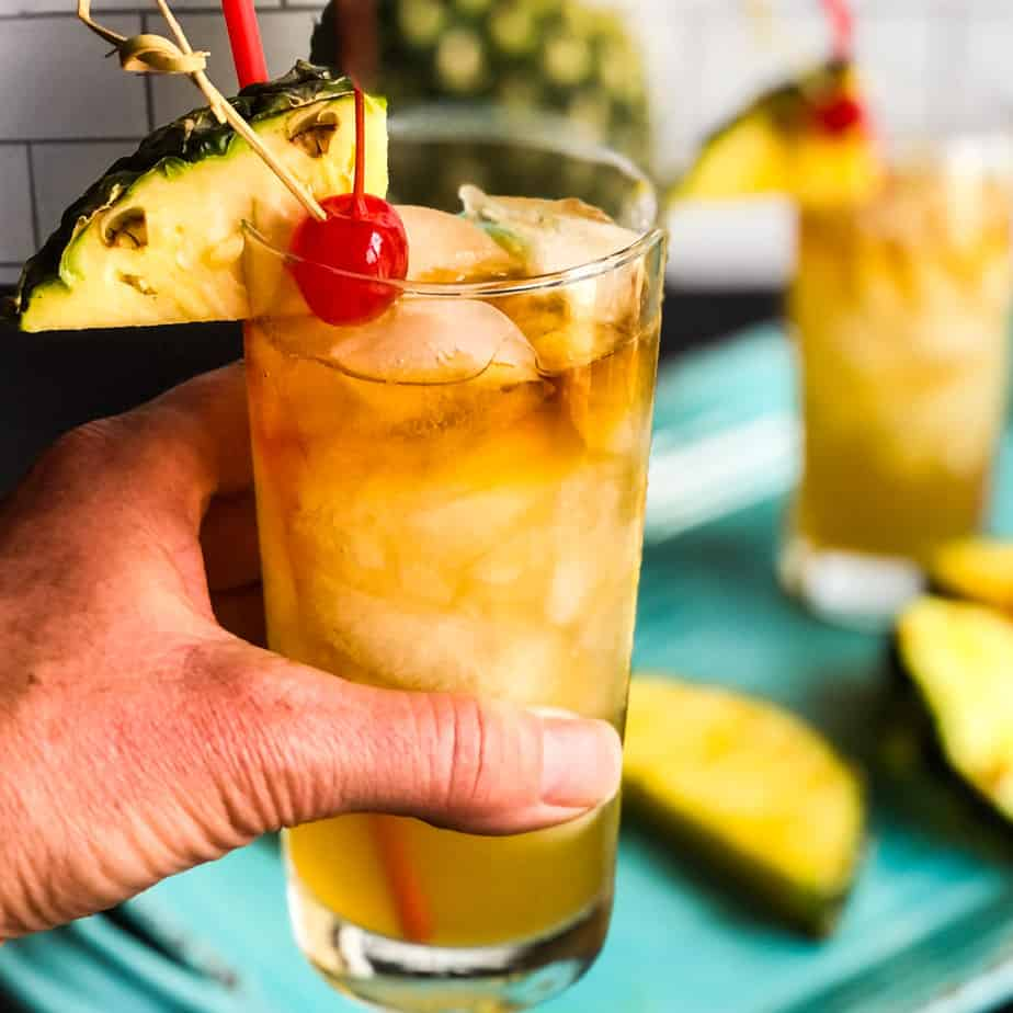 Hand holding a Mai Tai in front of a pineapple and second cocktail blurred in background.