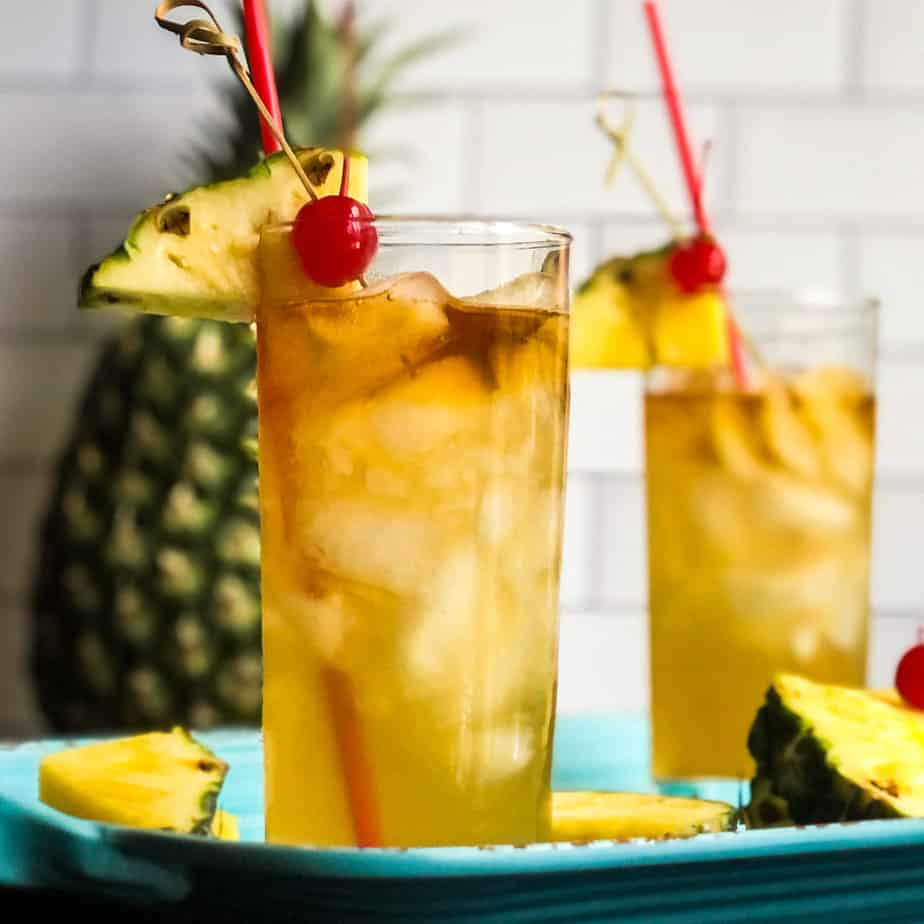 Close up of Mai Tai in a highball glass garnished with a pineapple wedge and cherry.
