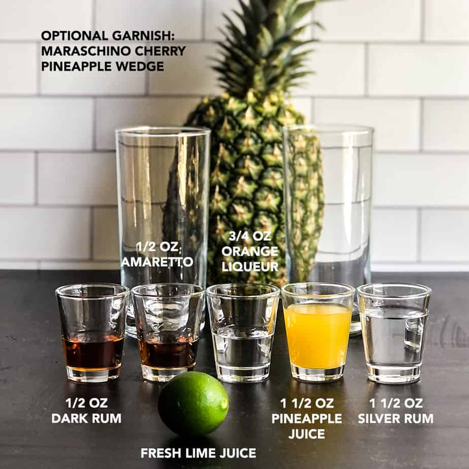 Ingredients for Mai Tai portioned into clear shot glasses in front of a pineapple.