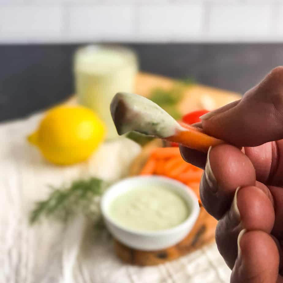 Hand holding a carrot dunked in creamy feta dressing.